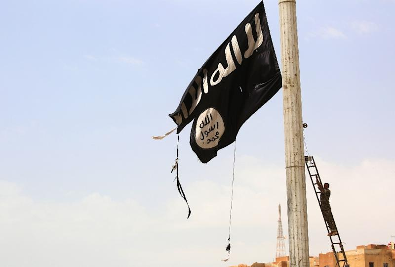 An Islamic State group flag in the Syrian town of Tabqa as it is being removed by a member of the US-backed Syrian Democratic Forces on April 30, 2017 (AFP Photo/DELIL SOULEIMAN)