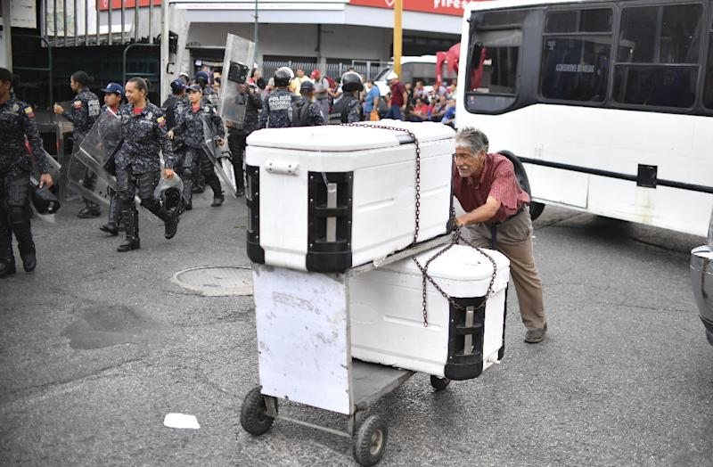 A man push a cart with coolers as Bolivarian National policemen are deployed to a subway station in Caracas, Venezuela on March 14, 2019 (AFP Photo/YURI CORTEZ)