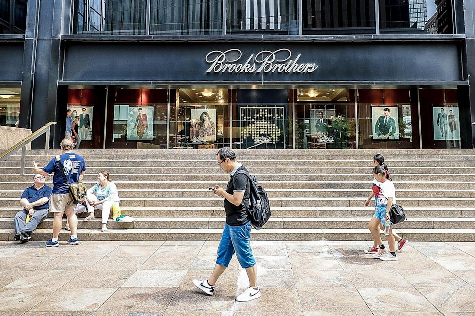 <p>A man uses his mobile device while others sit on the steps outside Brooks Brothers as people check out construction at the World Trade Center site in New York City on Aug. 18, 2018. (Photo: Gordon Donovan/Yahoo News) </p>