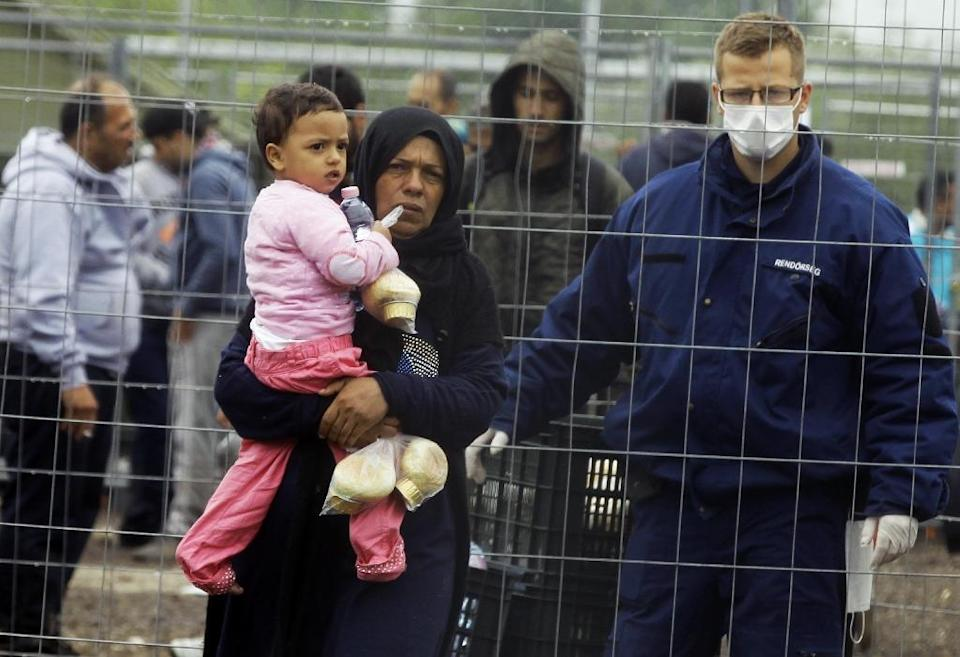 A migrant woman and child in a refugee camp near Roszke at the Hungarian-Serbian border on September 11, 2015 (AFP Photo/Peter Kohalmi)
