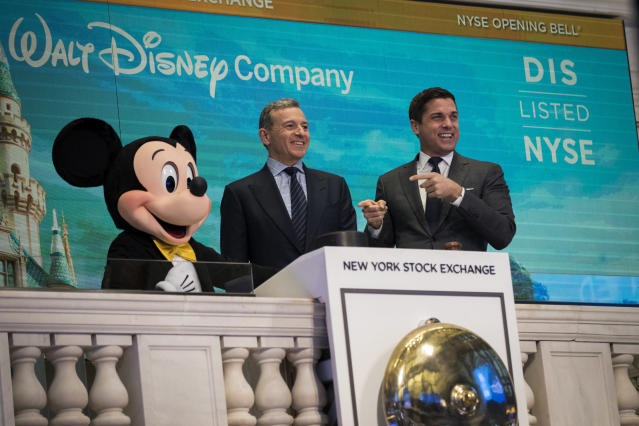 Disney CEO Bob Iger, middle, at the New York Stock Exchange with Mickey Mouse.