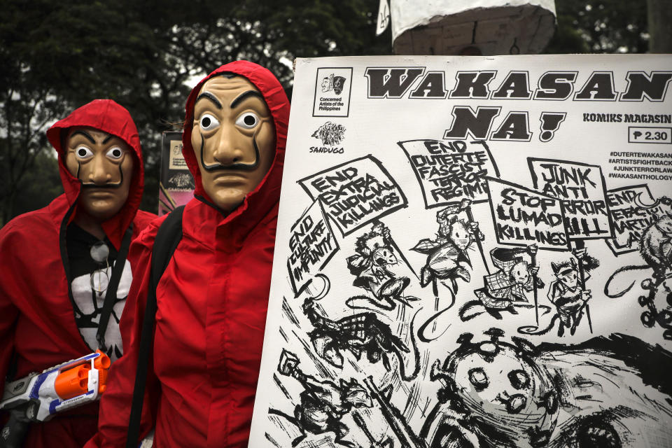 """Protesters wear masks as they hold a slogan that says """"End Now!"""" before marching towards the House of Representatives where Philippine President Rodrigo Duterte is set to deliver his final State of the Nation Address in Quezon city, Philippines on Monday, July 26, 2021. Duterte is winding down his six-year term amid a raging pandemic and a battered economy. (AP Photo/Gerard Carreon)"""