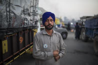 Farmer Harinder Singh, 28, stands for a photograph next to his tractor parked on a highway during a protest against new farm laws, at the Delhi-Haryana state border, India, Wednesday, Dec. 2, 2020. The protests started in September but drew nationwide attention last week when the farmers marched from northern Punjab and Haryana, two of India's largest agricultural states. Every day, thousands more join the protesters. (AP Photo/Altaf Qadri)