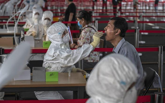 A Chinese epidemic control worker wears a protective suit as she performs a nucleic acid swab test for COVID-19 on a man at a government testing site in Xicheng District, Beijing - Kevin Frayer/Getty Images