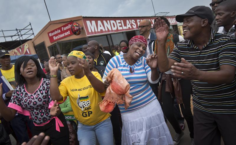Mourners sing and dance to celebrate the life of Nelson Mandela, in the street outside his old house in Soweto, Johannesburg, South Africa Friday, Dec. 6, 2013. Flags were lowered to half-staff and people in black townships, in upscale mostly white suburbs and in South Africa's vast rural grasslands commemorated Nelson Mandela with song, tears and prayers on Friday while pledging to adhere to the values of unity and democracy that he embodied. (AP Photo / Ben Curtis)