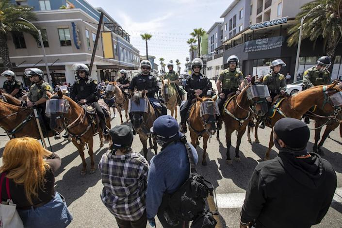 Protesters face a group of mounted police officers Sunday in Huntington Beach