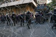 Riot police officers are seen at the police headquarters during a rally in Bangkok