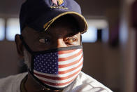 Bob Workman, a board of directors member at Veterans of Foreign Wars Post #1018, wears a stars and stripes protective mask and a Vietnam veteran hat as he prepares for a meeting, Monday, March 15, 2021, in Boston. Local bars and halls run by VFW and American Legion posts have fallen on hard times during the coronavirus pandemic. Organizers say many risk permanent closure after states ordered them, like other bars and halls, to shutter last spring. (AP Photo/Charles Krupa)