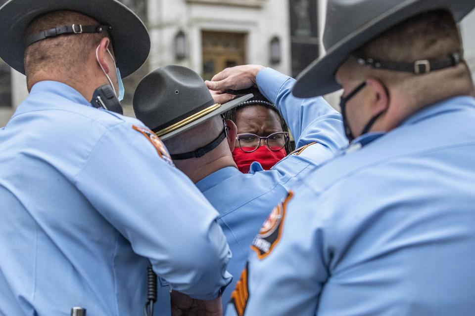 State Rep. Park Cannon, D-Atlanta, is placed into the back of a Georgia State Capitol patrol car after being arrested by Georgia State Troopers at the Georgia State Capitol Building in Atlanta, Thursday, March 25, 2021. Cannon was arrested by Capitol police after she attempted to knock on the door of the Gov. Brian Kemp office during his remarks after he signed into law a sweeping Republican-sponsored overhaul of state elections that includes new restrictions on voting by mail and greater legislative control over how elections are run. (Alyssa Pointer/Atlanta Journal-Constitution via AP)