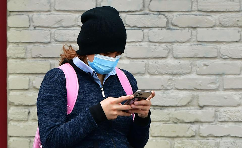 A woman wears a face mask while checking her cellphone in Los Angeles, on April 6, 2020. (Photo by FREDERIC J. BROWN/AFP via Getty Images)