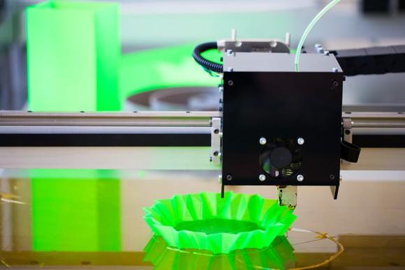 Close-up of a 3D printer printing a neon green plastic object that resembles a coffee machine filter.
