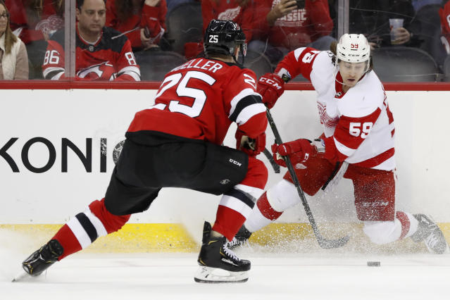 New Jersey Devils defenseman Mirco Mueller (25) challenges Detroit Red Wings left wing Tyler Bertuzzi (59) during the first period of an NHL hockey game, Thursday, Feb. 13, 2020, in Newark, N.J. (AP Photo/Kathy Willens)