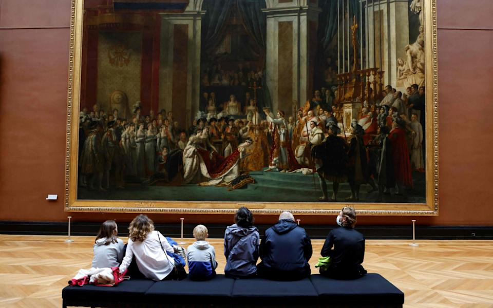"""In this file photo taken on October 14, 2020, sisitors wearing face masks look at the Oil on canvas paint """"The Coronation of Napoleon"""" - AFP"""