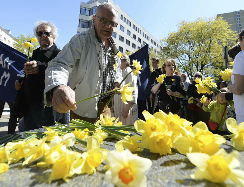 Warsaw residents lay daffodils, which have become the symbol of remembrance of the 1943 Warsaw Ghetto Uprising against the German Nazi, at a memorial site of the struggle, during anniversary observances in Warsaw, Poland, Friday, April 19, 2019.(AP Photo/Czarek Sokolowski)