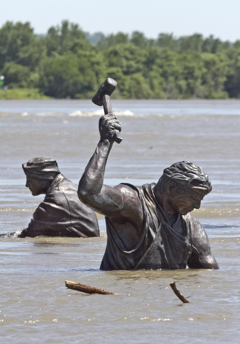 Statues of workers of various trades, part of the Monument for Labor by Matthew J. Placzek, stand in the rising waters of the Missouri River, in Omaha, Neb., Wednesday, June 15, 2011.  The Missouri River has been rising steadily for weeks as the Army Corps of Engineers increases the amount of water released from its dams to clear out heavy spring rain and snowmelt. The river is expected to reach 5 to 7 feet above flood stage in most of Nebraska and Iowa, and possibly higher in parts of Missouri. (AP Photo/Nati Harnik)