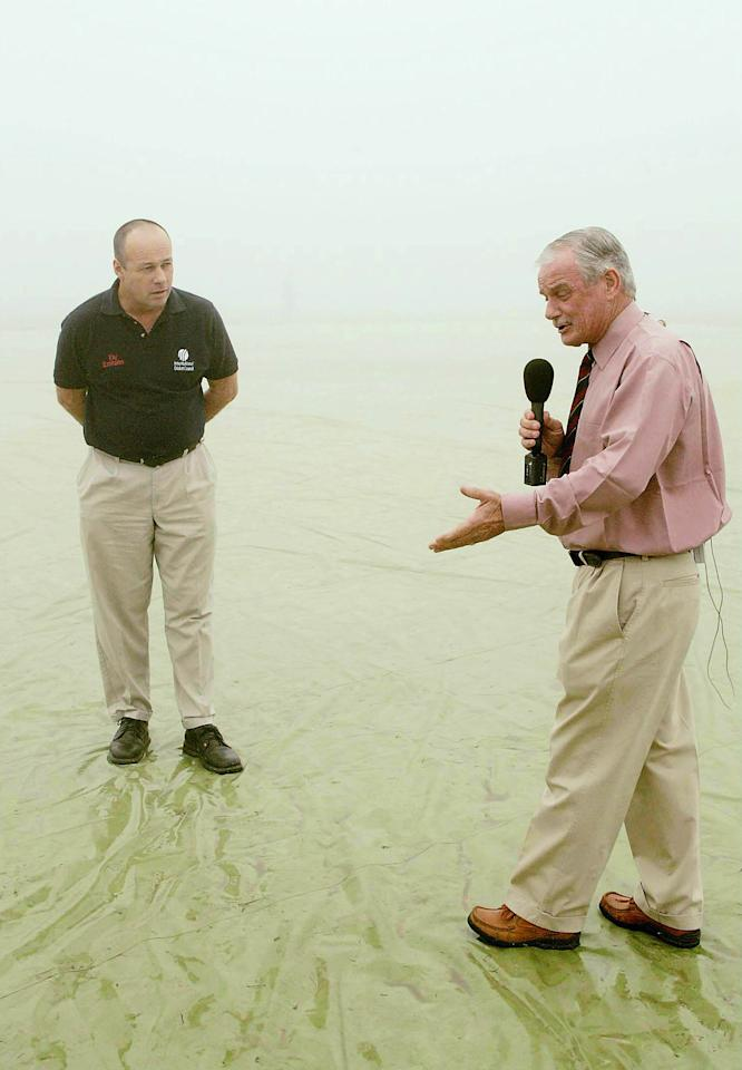 KANPUR, INDIA - NOVEMBER 22: (TOUCHLINE PHOTO IMAGES ARE AVAILABLE TO CLIENTS IN THE UK, USA AND AUSTRALIA ONLY)   Pitch reporter Robin Jackman talks with Umpire Daryl Harper in the fog during a delayed start on day three of the First test between India and South Africa at Green Park on November 22, 2004 in Kanpur, India. (Photo by Touchline/Getty Images)