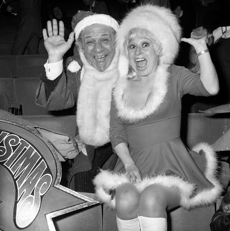 Carry On film stars Sid James and Barbara Winsdor welcome guests at a party for stars who are to perform on ITV during the Christmas period, at the New London Theatre.   (Photo by PA Images via Getty Images)