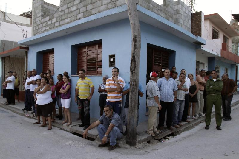 People wait outside the courthouse where Spanish citizen Angel Carromero is on trial in Bayamo, Cuba, Friday, Oct. 5, 2012. Authorities accused Carromero of speeding and charged him with the equivalent of vehicular manslaughter, and prosecutors asked the court for a seven-year sentence. The car crash killed a prominent Cuban dissident Oswaldo Paya and another dissident, Harold Cepero on July 22. A panel of judges will now consider the evidence and issue a ruling at an unspecified future date. (AP Photo/Franklin Reyes)