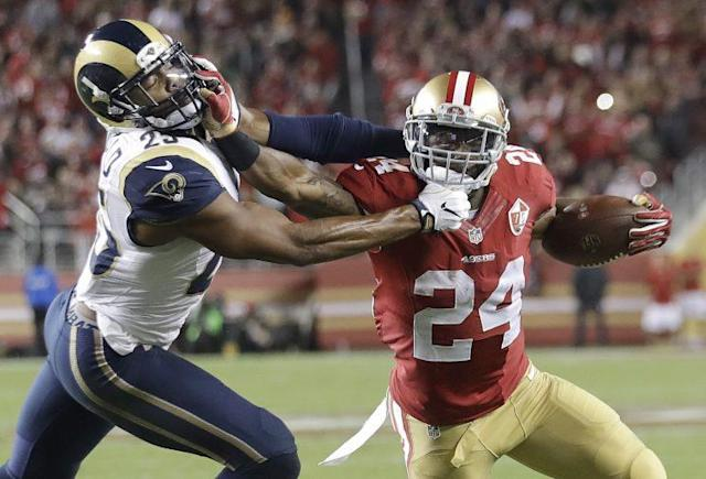 49ers RB Shaun Draughn (24) stiff arms Rams safety T.J. McDonald on a touchdown run (AP)