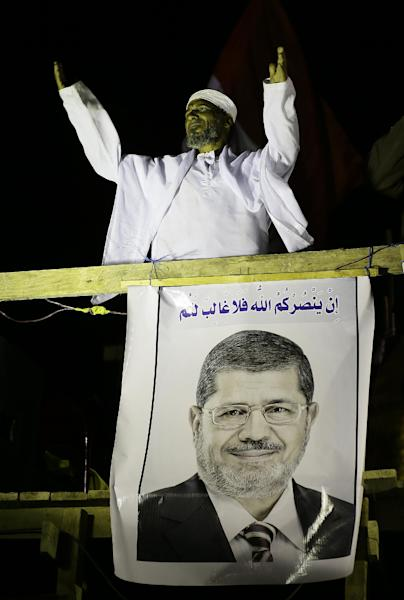 """A cleric addresses Islamist protesters supporting Egyptian President Mohammed Morsi, seen on poster, during a protest in front of the Media City complex in Giza, Egypt, Wednesday, Dec. 12, 2012. Egypt's main opposition alliance called for a """"No"""" vote in the referendum on a disputed constitution rather than a boycott, hours after Islamist President Mohammed Morsi's government forged ahead by starting overseas voting in diplomatic missions for expatriates. The Arabic writing is a verse from the Quran. (AP Photo/Hassan Ammar)"""