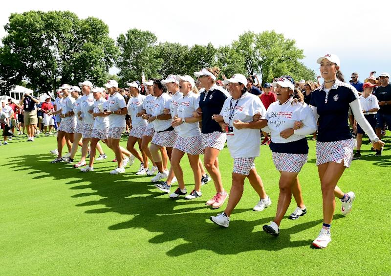 Team USA walk arm and arm up the 18th fairway after beating Team Europe in the Solheim Cup on August 20, 2017 (AFP Photo/Harry How)