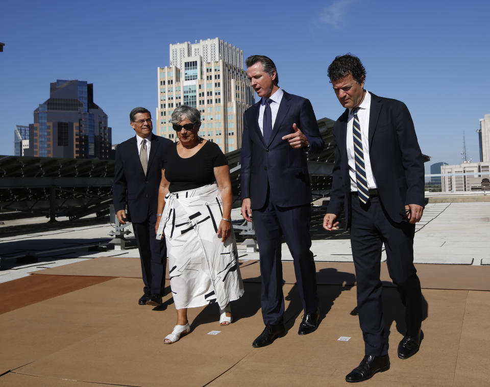 FILE - In this Aug. 13, 2019, file photo, California Gov. Gavin Newsom, second from right, tours the solar panels atop the building housing the California Environmental Protection Agency, accompanied by Attorney General Xavier Becerra, left, California Air Resources Board Chair Mary Nichols, and California EPA Director Jared Blumenfeld, right, in Sacramento, Calif. Nichols' term leading the state ARB ends in December 2020. She's held the role since 2007 after an earlier stint as chair in the early 1980s. (AP Photo/Rich Pedroncelli, File)