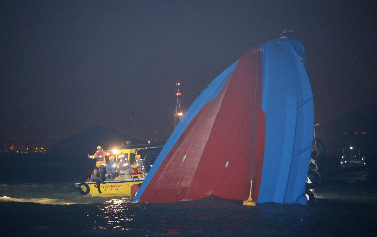 Rescuers check on a half submerged boat after it collided Monday night near Lamma Island, off the southwestern coast of Hong Kong Island Tuesday, Oct. 2, 2012. Authorities in Hong Kong have rescued 101 people after a ferry collided with a tugboat and sank. A local broadcaster says eight people died. (AP Photo/Kin Cheung)