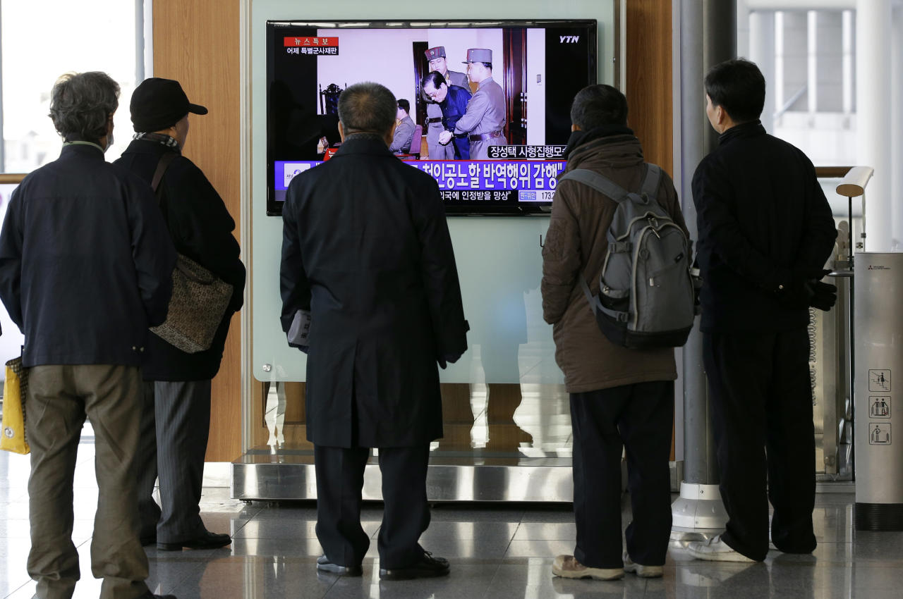 "People watch a live TV news program showing that North Korean leader Kim Jong Un's uncle Jang Song Thaek, second from right, is escorted by military officers during a trial in Pyongyang, North Korea Thursday, Dec. 12, 2013, at the Seoul Railway Station in Seoul, South Korea, Friday, Dec. 13, 2013. North Korea said Friday that it had executed Jang as a traitor for trying to seize supreme power, a stunning end for the leader's former mentor, long considered the country's No. 2 official. The letters on the left top, read ""North Korea Executed Jang Song Thaek after trial."" (AP Photo/Lee Jin-man)"