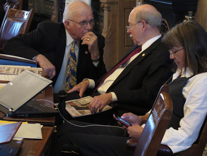 Kansas state Sen. Ralph Ostmeyer, left, a Grinnell Republican, consults with Senate Assessment and Taxation Committee Chairman Les Donovan, a Wichita Republican, center, during a debate on tax cuts, Tuesday, March 20, 2012, at the Statehouse in Topeka, Kan. To their right is Sen. Susan Wagle, a Wichita Republican. (AP Photo/John Hanna)