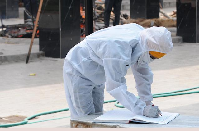 A family member of a person who died of COVID-19, seen in PPE overalls while completing formalities in Patiala. (Photo by Bharat Bhushan/Hindustan Times via Getty Images)