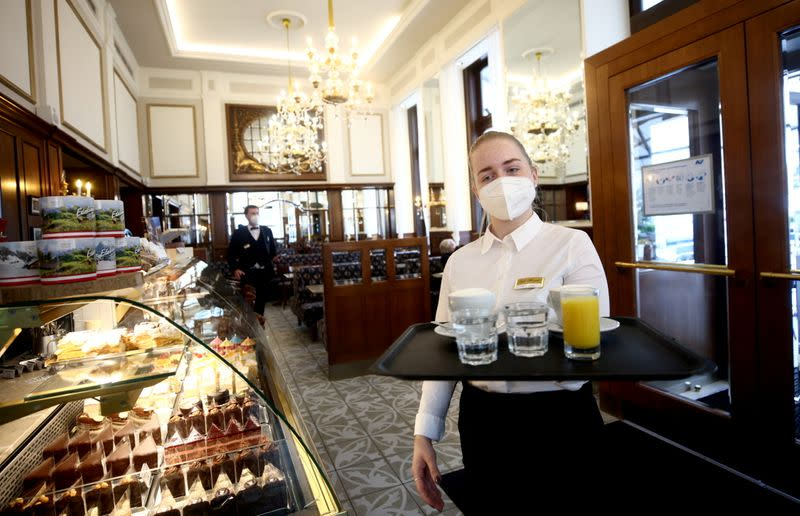 A waiter carries a tray with coffee and juice inside Cafe Mozart in Vienna
