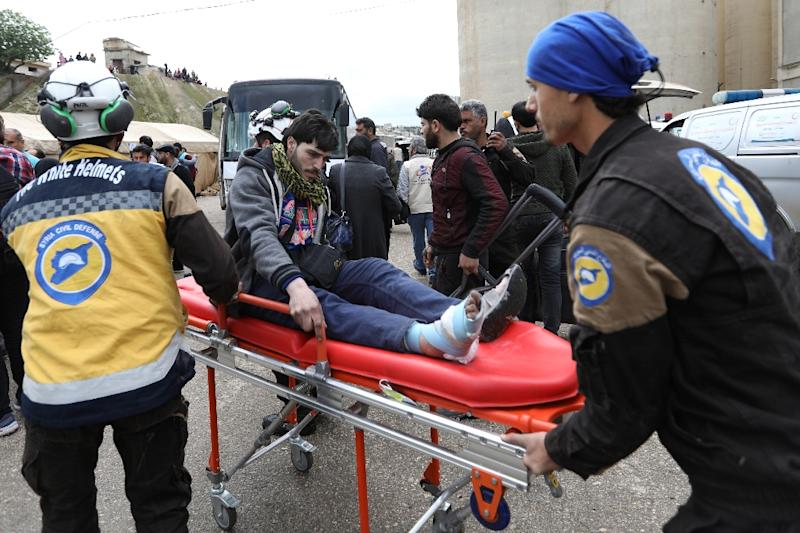 Syrian paramedics carry a wounded man upon his arrival in the village of Qalaat al-Madiq, north of Hama, on March 25, 2018, after he left the Eastern Ghouta enclave under an evacuation deal (AFP Photo/OMAR HAJ KADOUR)