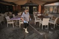 A staffer wearing a mask cleans the terrace of a shopping mall in La Caleta, in the Canary Island of Tenerife, Spain, Wednesday, Feb. 26, 2020. Worries over the ever-expanding economic fallout of the COVID-19 crisis multiplied, with factories idled, trade routes frozen and tourism crippled, while a growing list of countries braced for the illness to claim new territory. Even the Olympics, five months away, wasn't far enough off to keep people from wondering if it would go on as planned. (AP Photo)