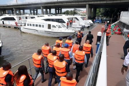 Uber officials walk with life vests at the five cowries terminal during the company's boat service launch in Lagos