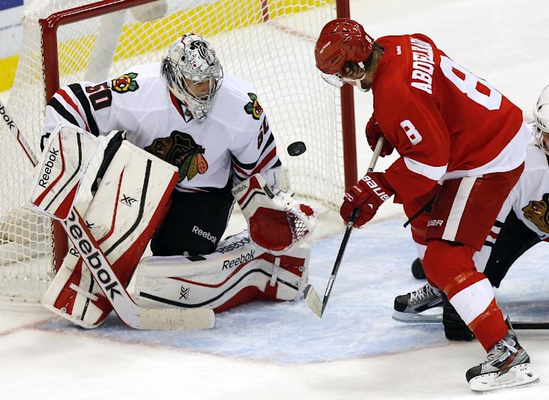 Detroit Red Wings' Justin Abdelkader (8) fails to get the puck past Chicago Blackhawks' Corey Crawford (50) in the third period of a preseason NHL hockey game Sunday, Sept. 22, 2013 in Detroit. The Blackhawks defeated the Red Wings 4-3. (AP Photo/Duane Burleson)