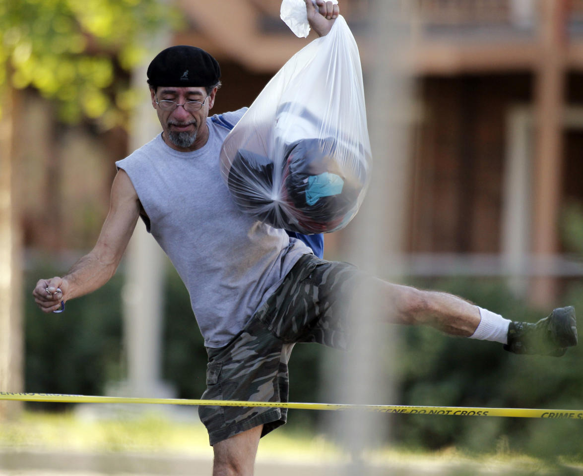 "Roberto Martinez hops over the police tape as he carries his belongings from his home near the apartment of alleged gunman James Holmes Friday, July 20, 2012 in Aurora, Colo. Authorities report that 12 died and more than three dozen people were shot during an assault at the theatre during a midnight premiere of ""The Dark Knight."" Colorado firefighters are monitoring the Aurora apartment building for gases in an effort to determine what chemicals they say 24-year-old James Holmes might have used to trap the place _ in case the materials go off. (AP Photo/Alex Brandon)"