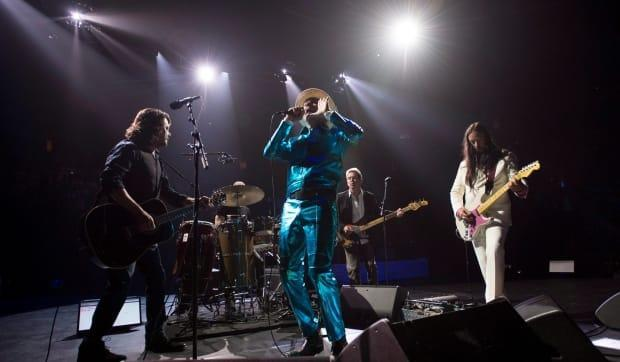 Frontman of the Tragically Hip, Gord Downie, centre, leads the band through a concert in Vancouver on July, 24, 2016. The Hip will return to the stage without Downie, who died in 2017, but with indie-rocker Feist for the 50th annual Juno Awards. (Jonathan Hayward/The Canadian Press - image credit)