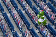 The Phillie Phanatic tries to cheer the team on while surrounded by the cutouts of fans in the seats during a baseball game against the New York Mets, Sunday, Aug. 16, 2020, in Philadelphia. The Phillies did their best to compensate for the cold, sterile atmosphere by putting out an array of cardboard cutouts in the stands. (AP Photo/Chris Szagola)