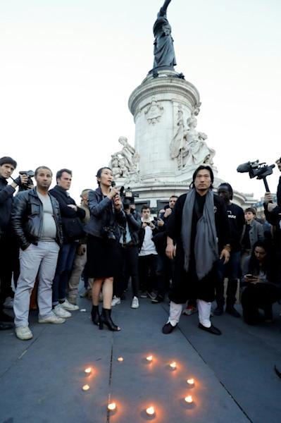 A woman speaks next to candles during a demonstration for justice on the Place de la Republique on March 30, 2017 following the death of Chinese Liu Shaoyo during a police intervention