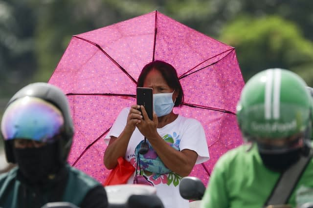 A woman wearing a mask takes a photo of a checkpoint (Aaron Favila/AP)