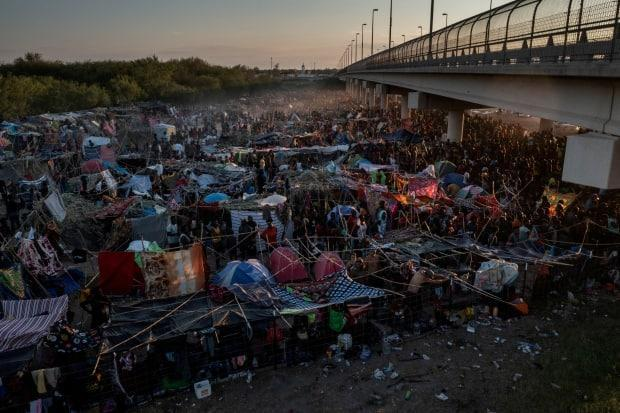 Migrants take shelter along the Del Rio International Bridge in Texas at sunset as they wait to be processed after crossing the Rio Grande river into the U.S. from Ciudad Acuna, Mexico, on Sept. 19. (Adrees Latif/Reuters - image credit)