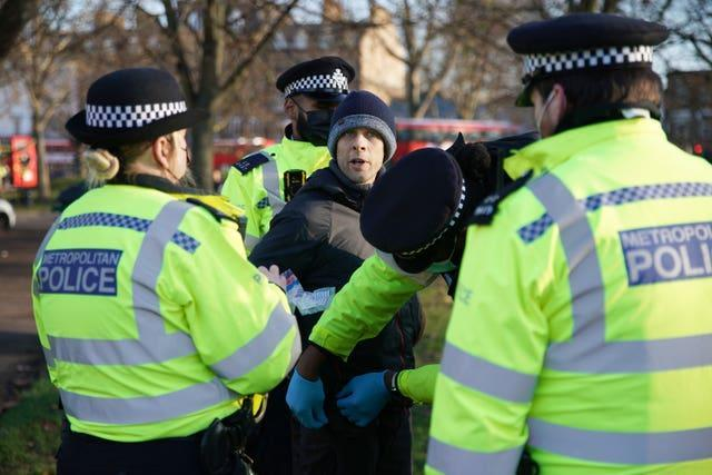 Police detain a man during an anti-lockdown protest in Clapham Common, London, on Saturday