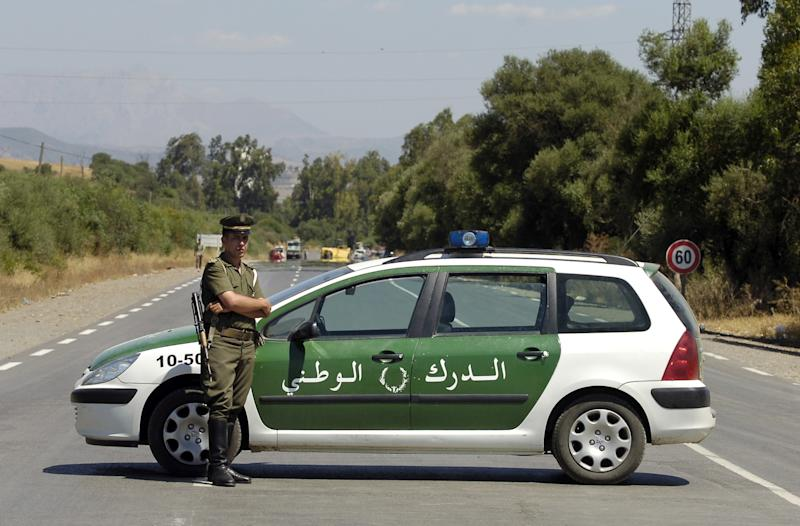 An Algerian policeman stands guard as security forces block the road to Lakhdaria, southeast of Algiers on July 11, 2007