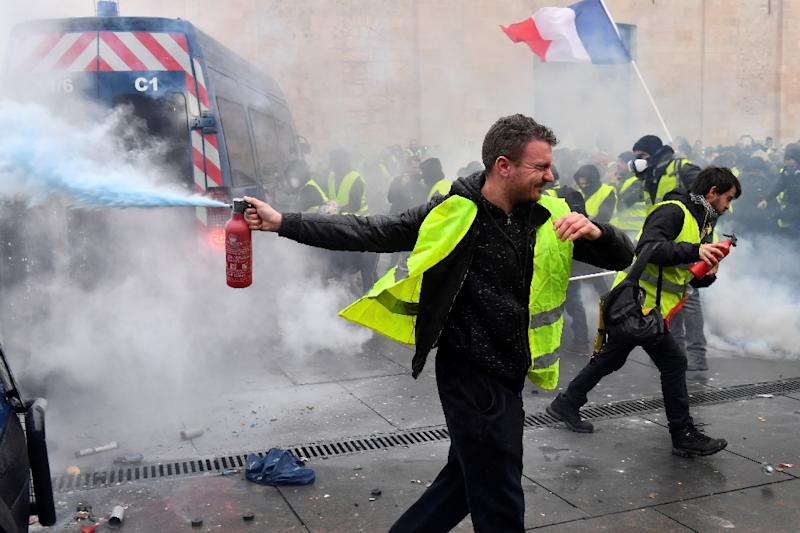 Yellow Vests protesters clash with riot police forces during a demonstration against rising oil prices and living costs in Bordeaux, southwestern France, on December 1, 2018