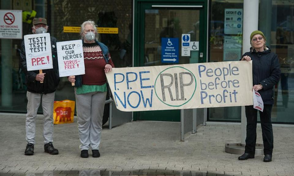 People holding banners saying 'PPE now' and 'People before profit'.