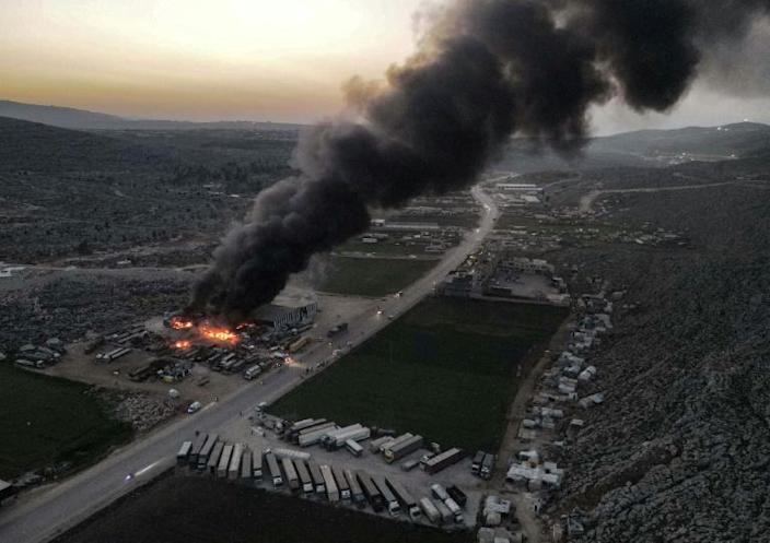 Smoke billows from burning trucks and freight vehicles on March 21, 2021 in the aftermath of air strikes at a depot near the Bab al-Hawa, the sole border crossing into Syria
