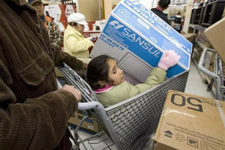 A girl sits in a shopping cart as she holds a television in a Walmart store in Oakland