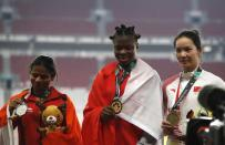 Athletics - 2018 Asian Games - Women's 100m Final - GBK Main Stadium – Jakarta, Indonesia – August 26, 2018 – Gold medallist Edidiong Odiong of Bahrain, silver medallist Dutee Chand of India and bronze medallist Wei Yongli of China pose during the medal ceremony. REUTERS/Darren Whiteside