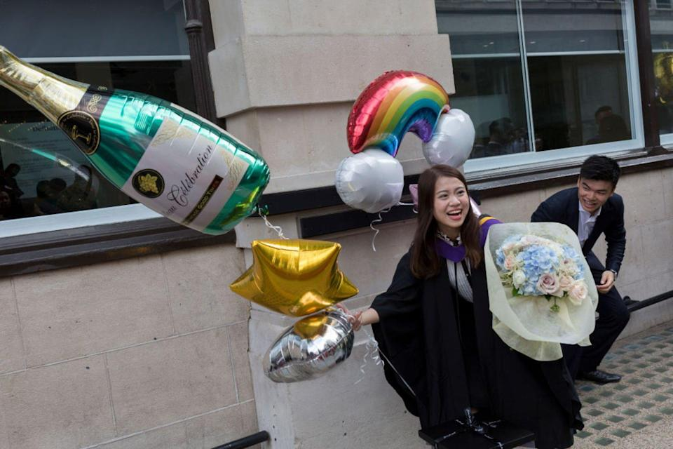 Hillary Chung, a 21 year-old Law graduate from Hong Kong, celebrates her graduation outside the London School of Economics. Photo: Getty Images