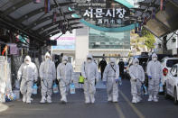 """Workers wearing protective gears spray disinfectant as a precaution against the COVID-19 at a local market in Daegu, South Korea, Sunday, Feb. 23, 2020. South Korea's president has put the country on its highest alert for infectious diseases and says officials should take """"unprecedented, powerful"""" steps to fight a viral outbreak. (Im Hwa-young/Yonhap via AP)"""